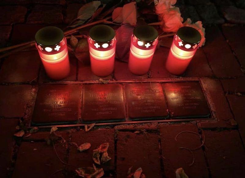 Mit Rosen und Kerzen geschmückte Stolpersteine.